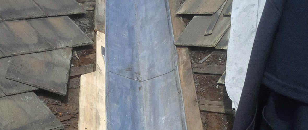 Lead flashing showing old tiles and new carpentry